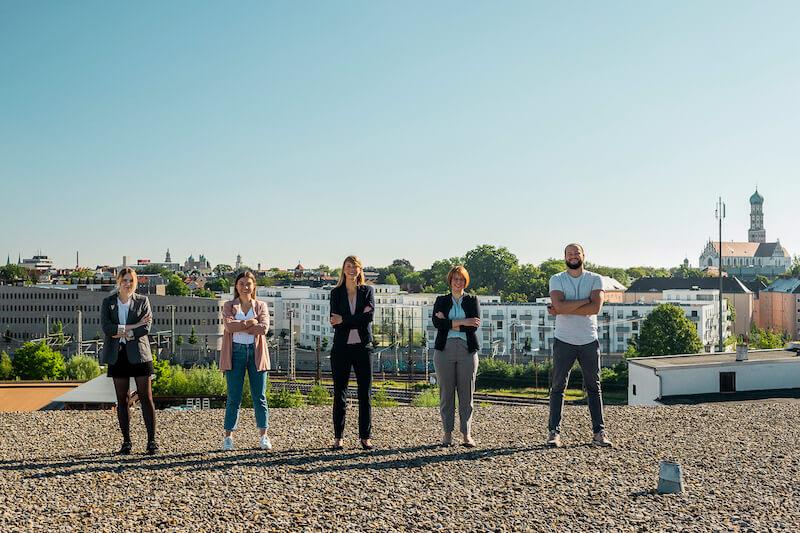 Agentur Charismarcom Team vor Augsburg Skyline